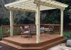 A cozy free-standing deck with shade pergola is an ideal outdoor space for a sma...