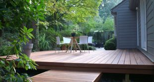 Decking surrounded by plants, grey and white house